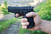 foto of pistols  - Detail of mans hand holding automatic pistol - JPG