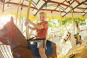 stock photo of carnival ride  - Two cute kids having fun while riding a carousel at an amusement park or carnival - JPG