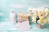 stock photo of text-box  - Background with colorful narcissus flowers candles box with present and empty tag for text on turquoise painted wooden planks - JPG