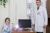 foto of infirmary  - Teenage girl checks sight at the reception of an ophthalmologist - JPG