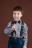 image of lollipop  - handsome child holding lollipop in hand isolated on brown background - JPG
