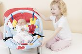 stock photo of little sister  - portrait of a little girl with her baby sister sleeping in a chair - JPG