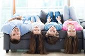 picture of upside  - Family lying upside down on sofa  - JPG