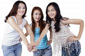 pic of joining hands  - Friendship of three beautiful female students joining hands together isolated on white - JPG