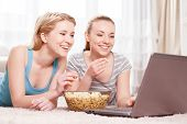 picture of pajamas  - Pajama party. Two young beautiful blond girls wearing pajamas lying on the floor eating popcorn and looking at the laptop