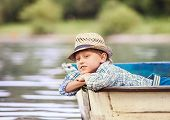 foto of old boat  - Dreaming boy lying in old boat on the river