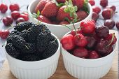 stock photo of mulberry  - Group of fresh spring fruits together black mulberries cherries and strawberries - JPG