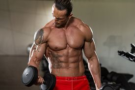 stock photo of bicep  - Muscular Mature Man Doing Heavy Weight Exercise For Biceps With Dumbbells In Modern Fitness Center - JPG