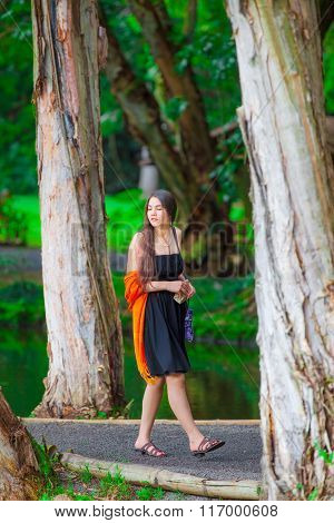 Teen girl in black sundress walking on wooded path