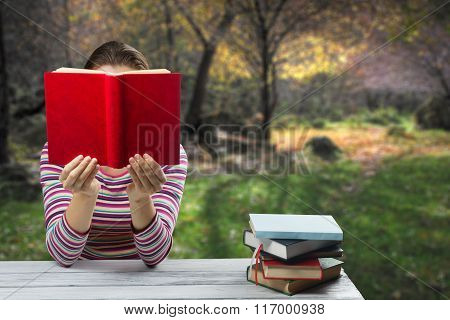 Young woman reading a book and covering her face ,sitting by wooden table with stack of colorful har