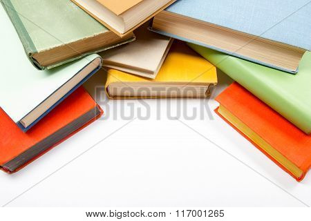Top view of old used colorful hardback books on white table. Back to school.