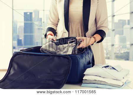 woman packing formal male clothes into travel bag