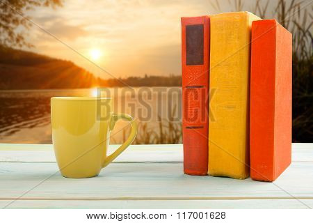 Stack of colorful books and cup at wooden table on natural blurred background. Back to school. Copy