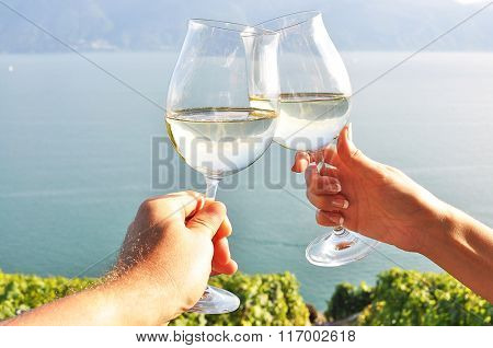 Two hands holding wineglases against Geneva lake, Switzerland