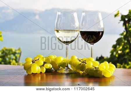 Two wineglasses and grapes against Geneva lake. Lavaux region, Switzerland.