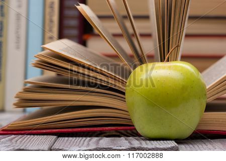 Open book, hardback books and green apple on wooden table. Back to school. Copy space