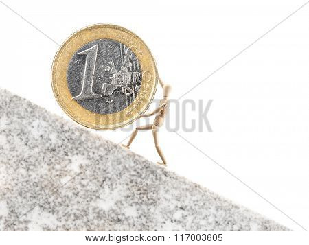 One Euro coin being rolled uppwards on inclined plane by wooden dummy on white background