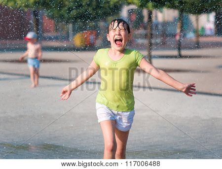 Hot summer in the city - girl is running through fountains
