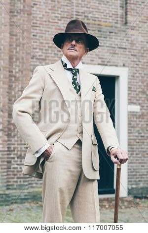 Well Dressed Senior Man Standing With Cane In Front Of Building.