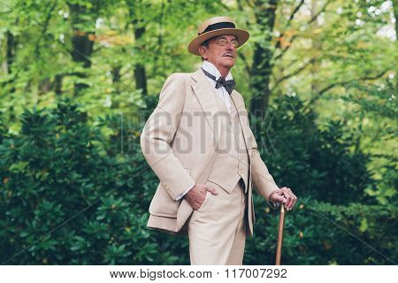 Wealthy Senior Man In Suit Standing With Cane In Garden.
