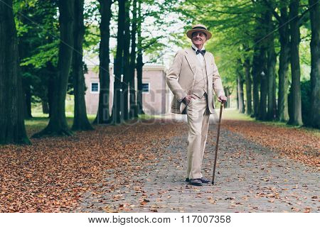 Smiling Wealthy Senior Retro Dandy In Suit Standing With Cane In Avenue.