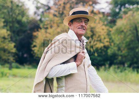 Smiling Senior Vintage Businessman Holding Jacket Over Shoulder Standing In Garden.