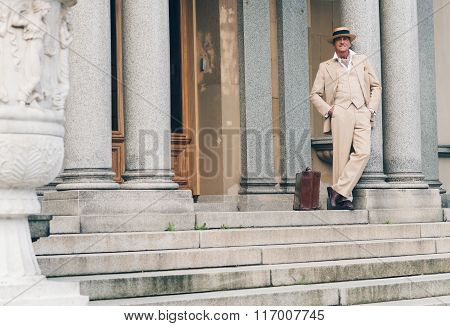 Retro Commercial Traveler Waiting On Stairs Leaning Against Column.