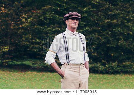 Senior Retro Fashion Man Standing In Garden.