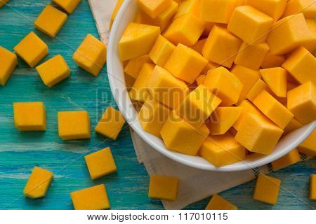 fresh pumpkin cut into pieces on wooden background food recipes