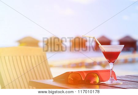 cocktail, touch pad and glasses on beach resort