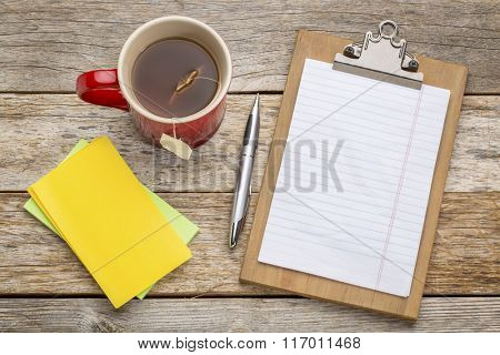 blank paper on clipboard  with a pen, tea and sticky notes against rust wood table- office concept