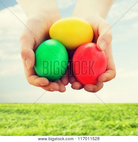close up of kid hands holding colored eggs