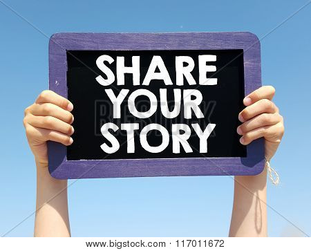 Hands holding blackboard with written Share your story