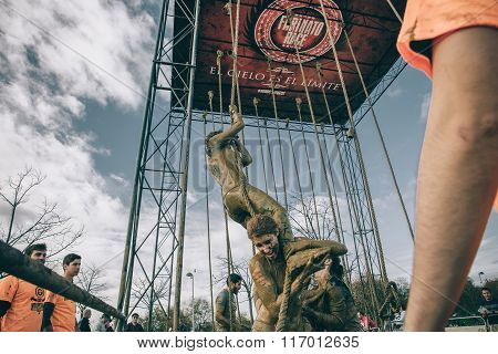 Team helping woman to climbing rope in a test of obstacle race