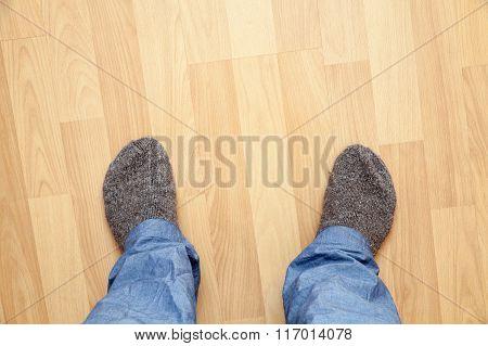 Male Feet In Blue Pants And Gray Woolen Socks