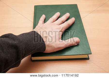 Male Hand Laying On Book, Swear Concept