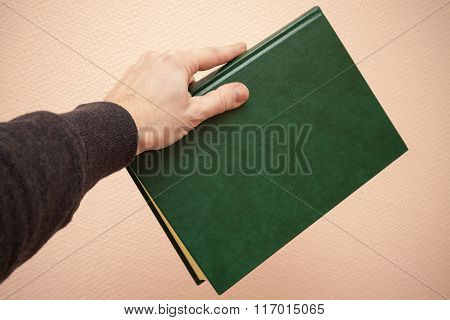 Book With Empty Dark Green Cover In Male Hand