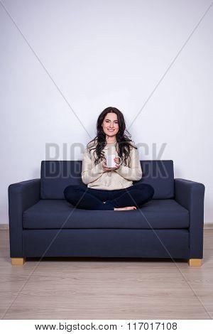 Young Woman Sitting On Sofa With Mug Of Tea At Home