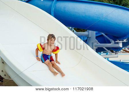 little boy having fun on waterslide pool