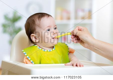 happy kid girl eating food with spoon