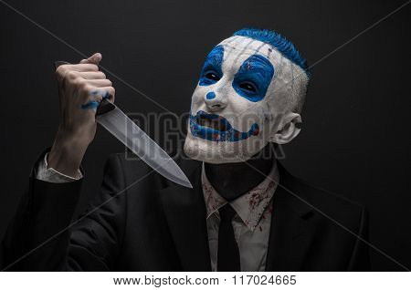 Terrible Clown And Halloween Theme: Crazy Blue Clown In A Black Suit With A Knife In His Hand Isolat