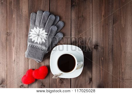 Top View Of Cup Of Black Coffee With  Gloves On Wooden Background