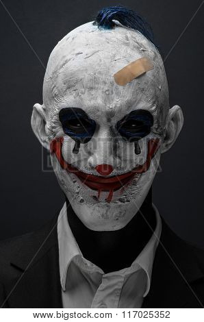 Terrible Clown And Halloween Theme: Crazy Terrible Blue Clown In Black Suit Isolated On A Dark Backg