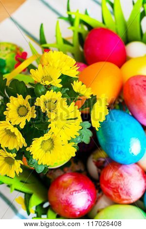 Vibrant holiday background. Still life with nice spring yellow flowers and colorful Easter eggs