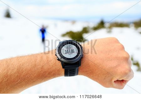 Runner On Mountain Winter Trail Looking At Stopwatch, Activity Monitor
