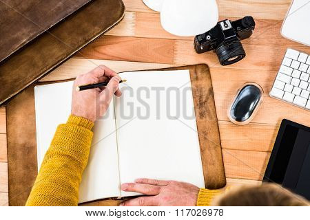 Above view of man writing on notebook on wooden desk