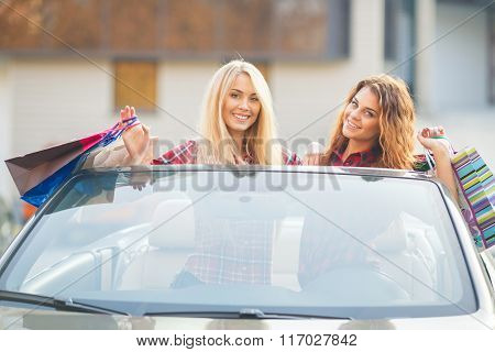 Girls with shopping bags in the convertible.