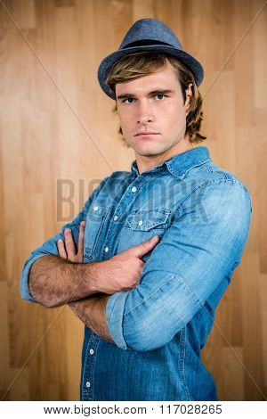 Serious hipster crossing his arms against wooden wall
