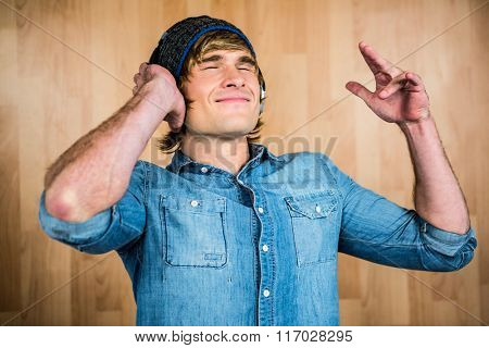 Cheerful hipster listening to music with hands on ears