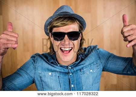 Cheerful hipster wearing sunglasses against wooden wall